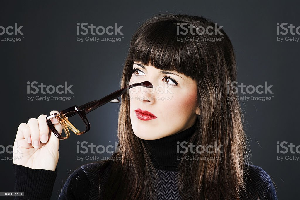 Young woman putting on a pair of heavy rimmed glasses. stock photo