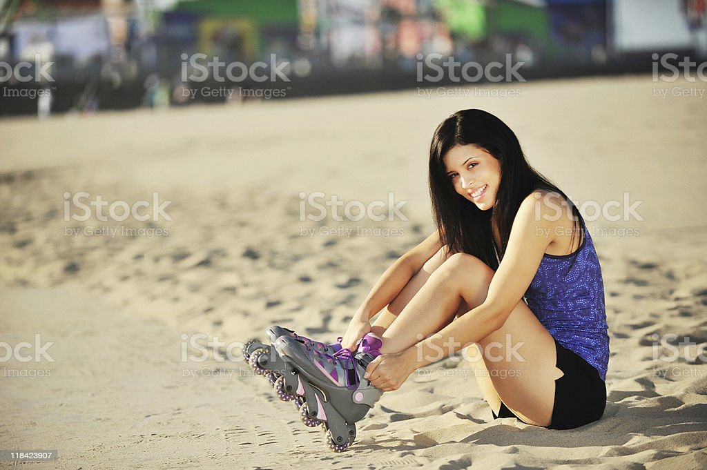 Young Woman Putting on Rollerblades at Santa Monica Beach royalty-free stock photo