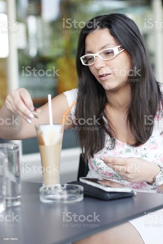 Young woman putting sugar in her coffee stock photo