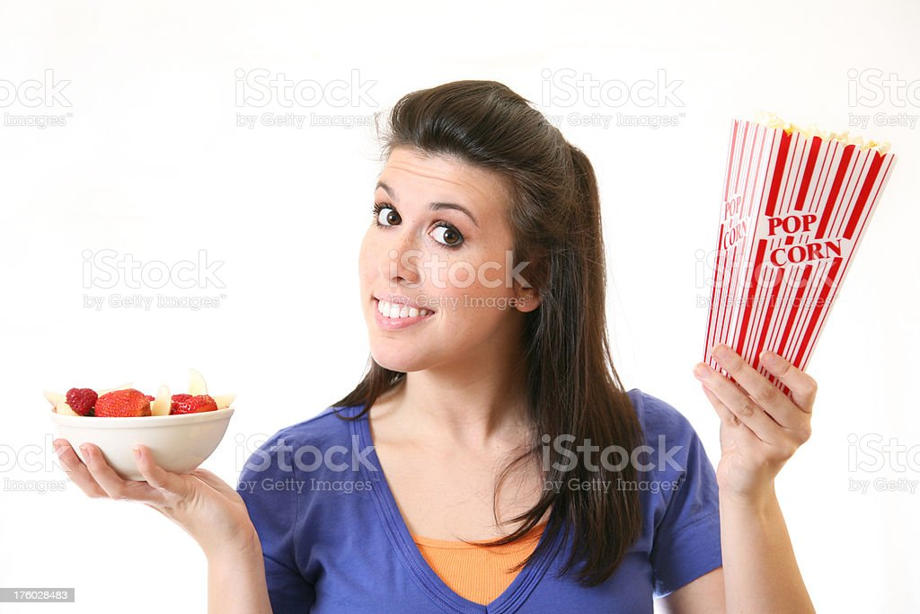Young Woman Questioning Healthy Versus Non-Healthy Food stock photo