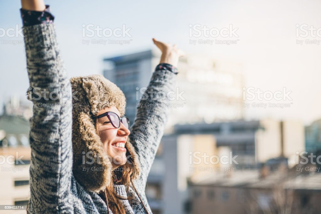 Young woman raising hands in the city stock photo