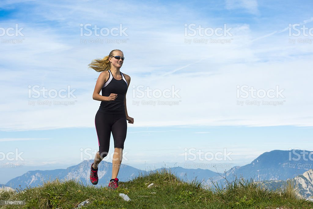 Young woman reaching the mountain peak stock photo