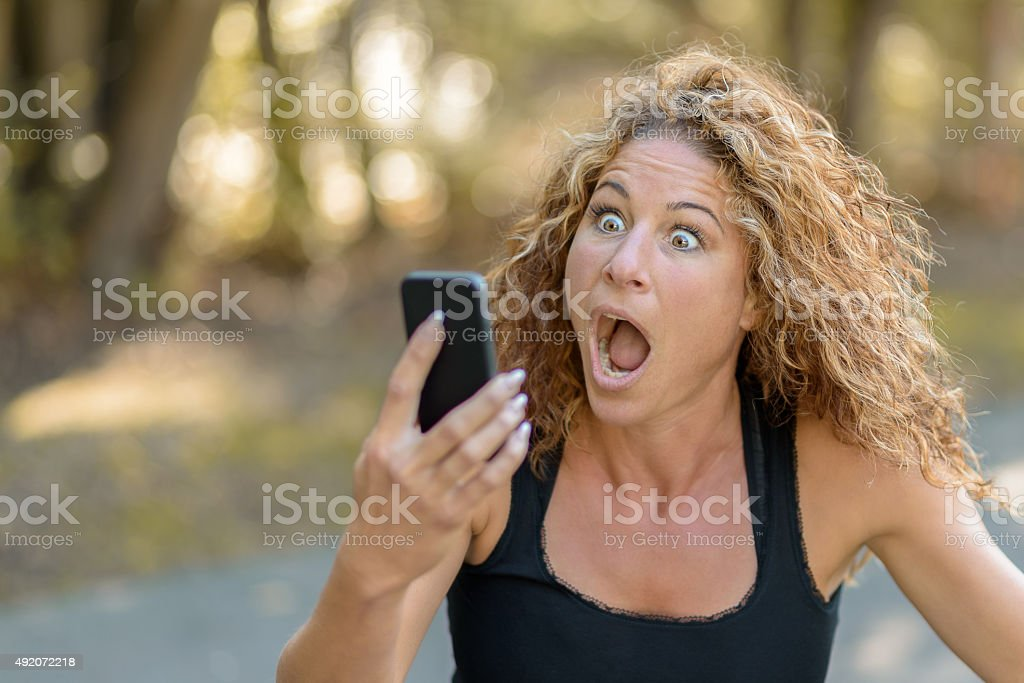 Young woman reacting in horror to a text message stock photo