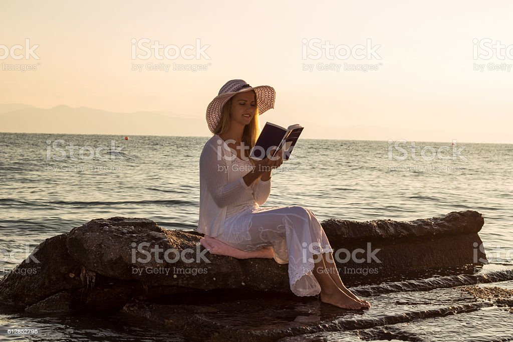 Young woman read book during beach vacation stock photo