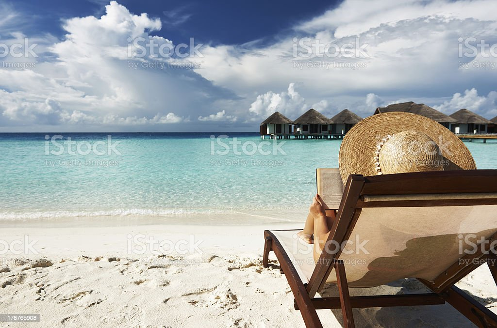 Young woman reading a book at beach royalty-free stock photo