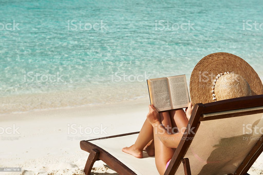 Young woman reading a book at beach stock photo