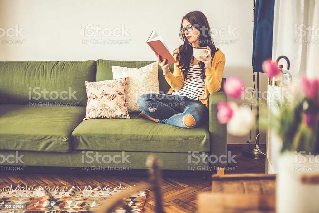 Young woman reading a book at home stock photo