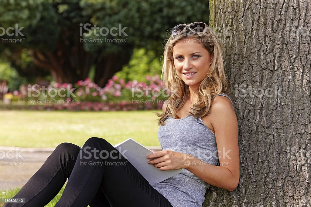 Young woman reading a book at the park royalty-free stock photo