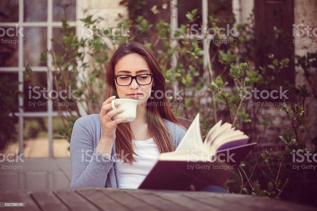 Young woman reading a book at the veranda stock photo