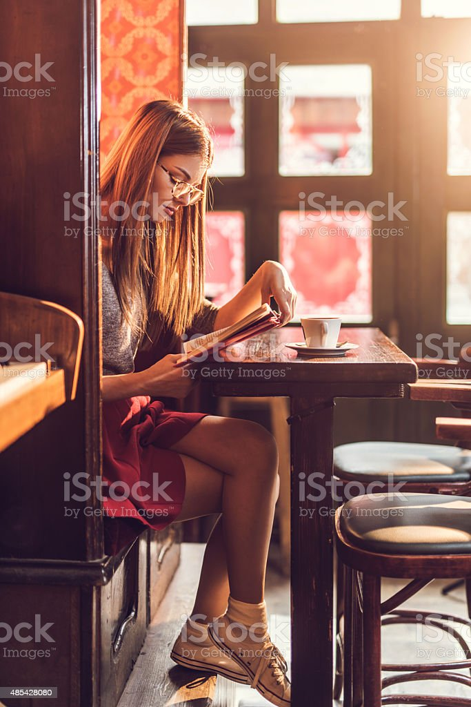 Young woman reading a book in a cafe. stock photo