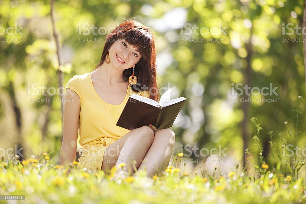 Young woman reading a book in the park with flowers royalty-free stock photo