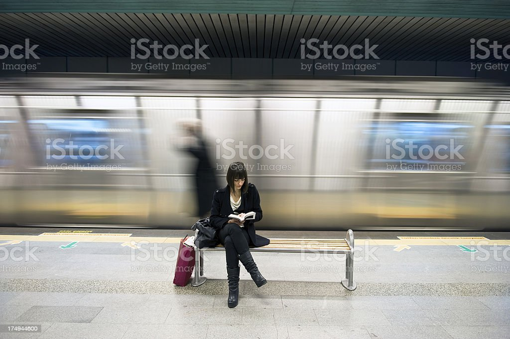 Young woman reading a book in the subway station royalty-free stock photo