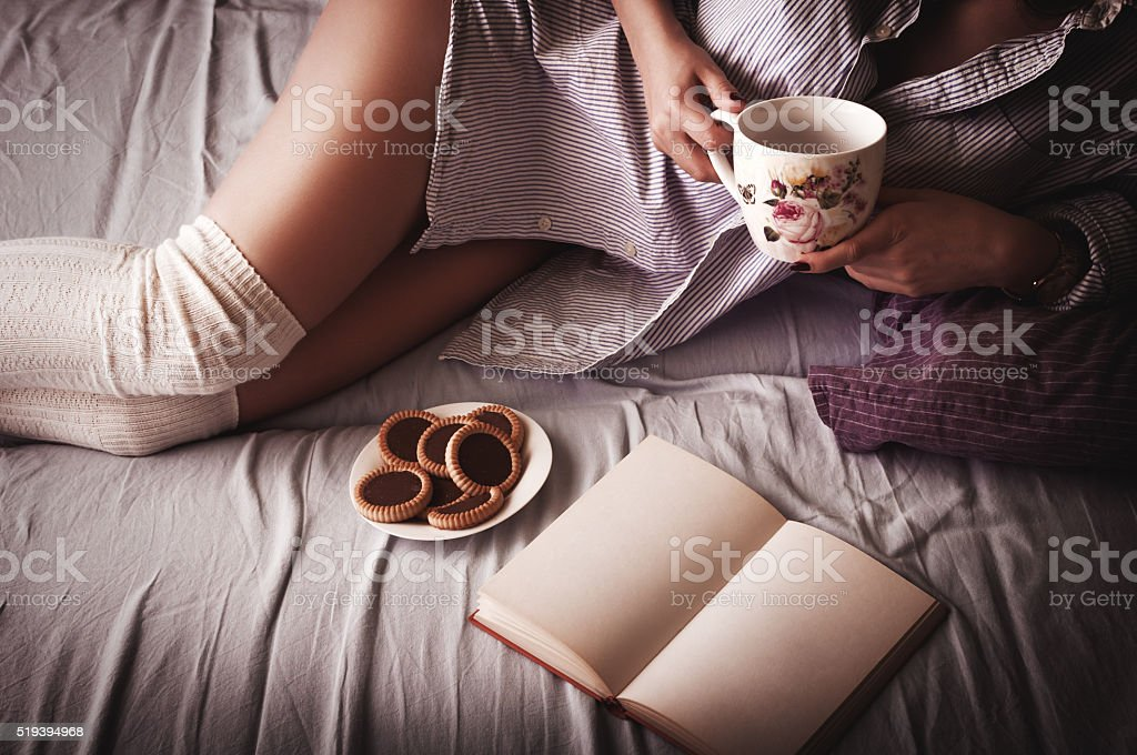 Young woman reading a book on bed stock photo