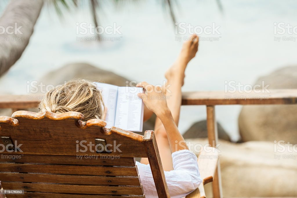 Young woman reading a book while relaxing on tropical island stock photo