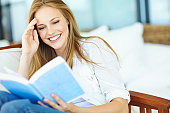 A young woman reading a book while smiling and laughing