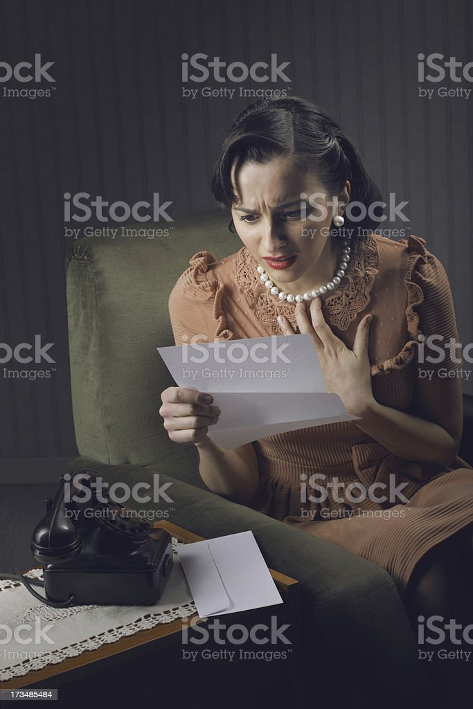 Young woman reading a letter with worried expression royalty-free stock photo