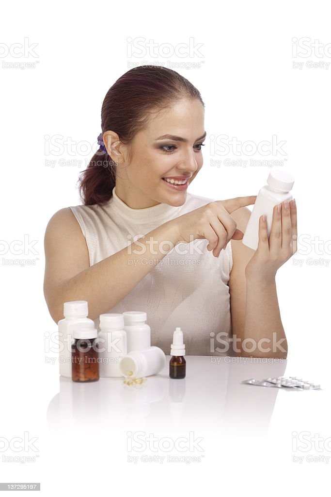 Young woman reading a prescription on the pill bottle. stock photo