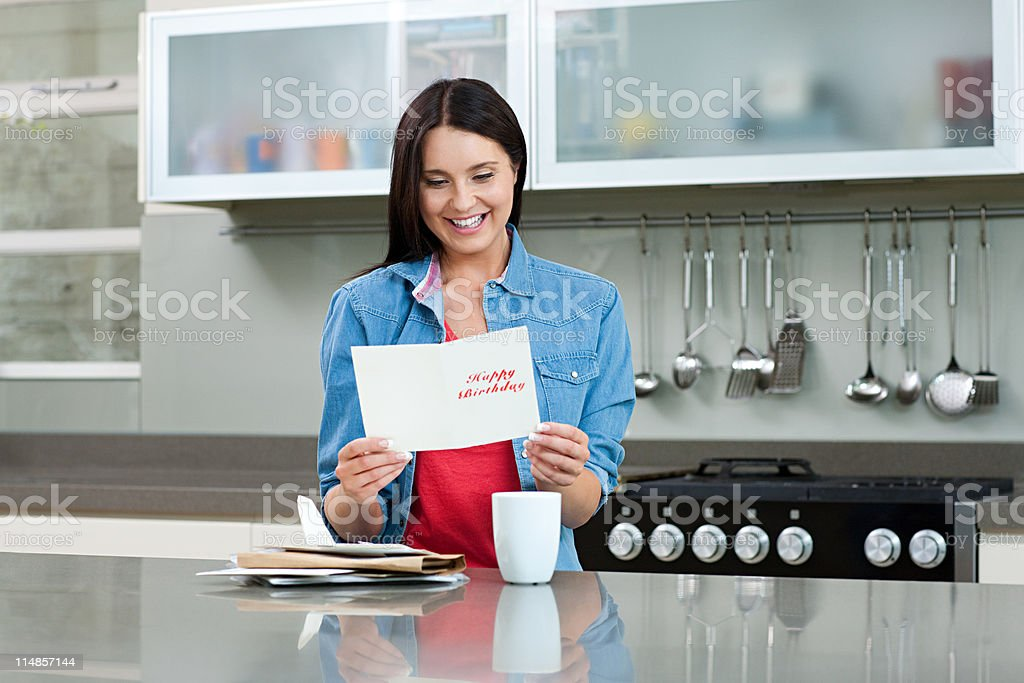 Young woman reading birthday card stock photo