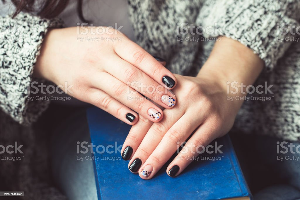 Young woman reading book, close-up, on home interior stock photo