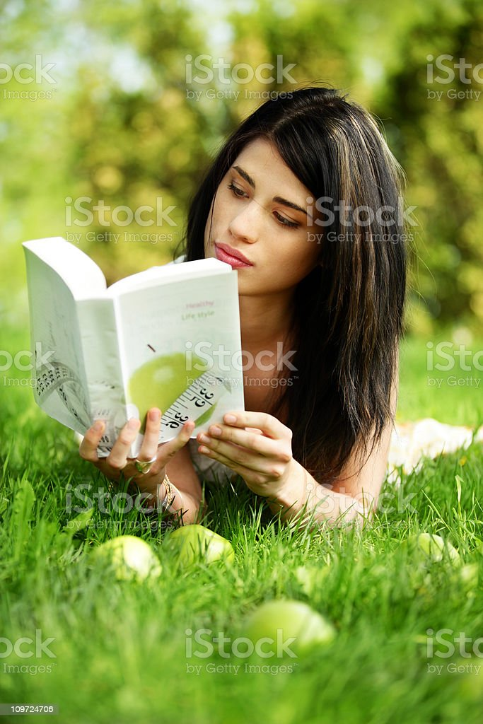 Young Woman Reading Book in Grass royalty-free stock photo