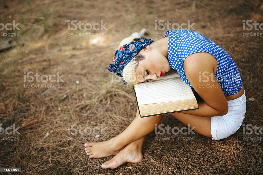 Young woman reading book in nature stock photo