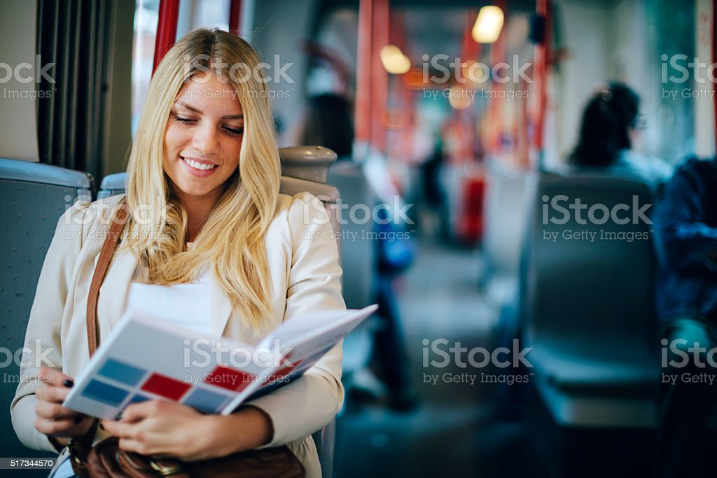Young Woman Reading Book In Public Transportation. stock photo