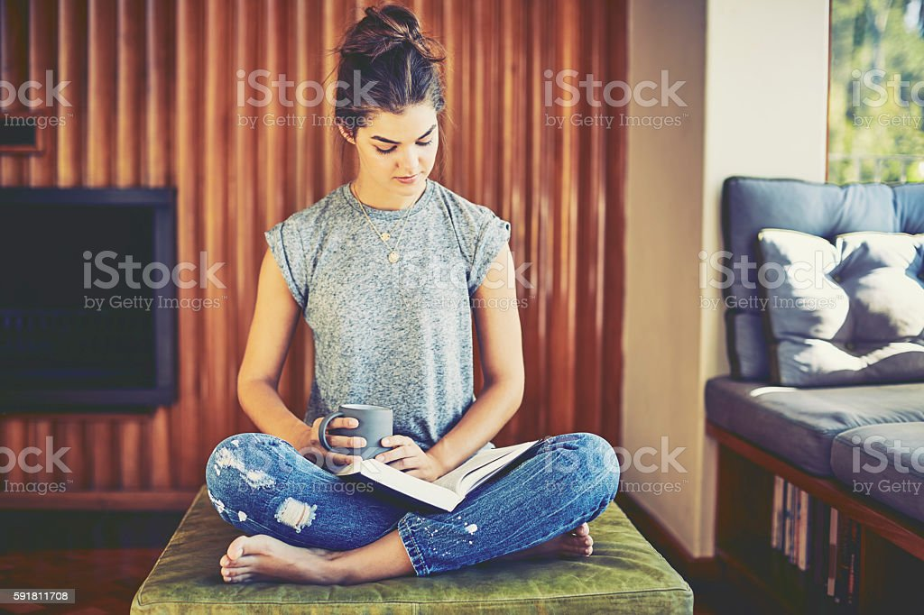 Young woman reading book while holding coffee cup at home stock photo