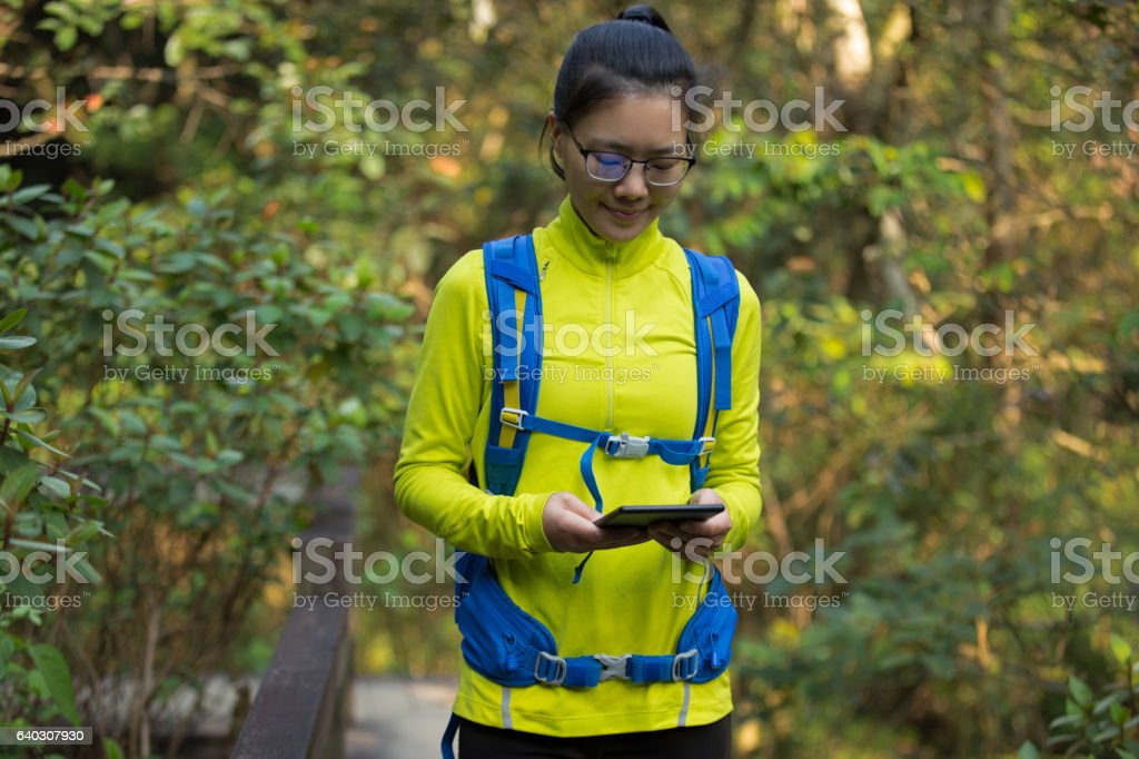 young woman reading ebook on park stock photo