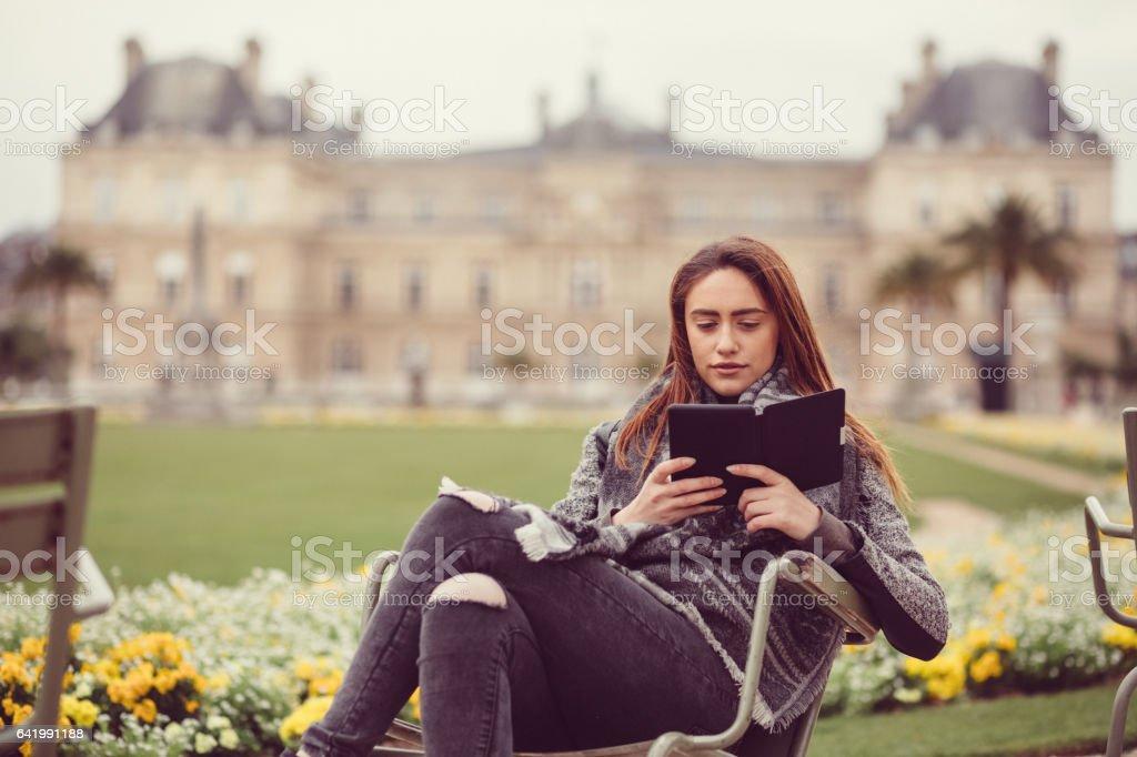 Young woman reading e-book outside stock photo