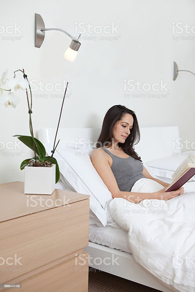 Young woman reading in bed royalty-free stock photo