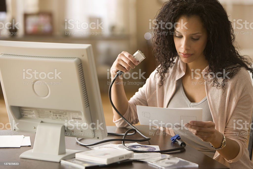 Young woman reading instructions on how to build PC stock photo