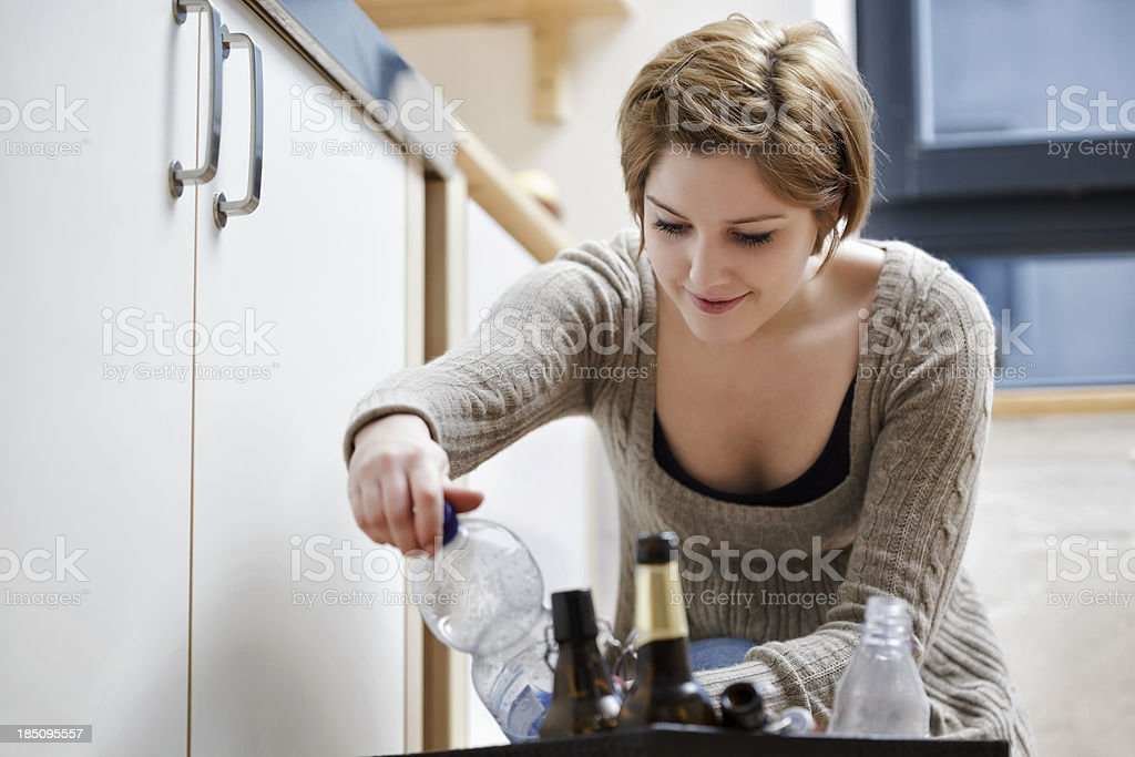 Young Woman Reading Labels on Recycleable Bottle royalty-free stock photo