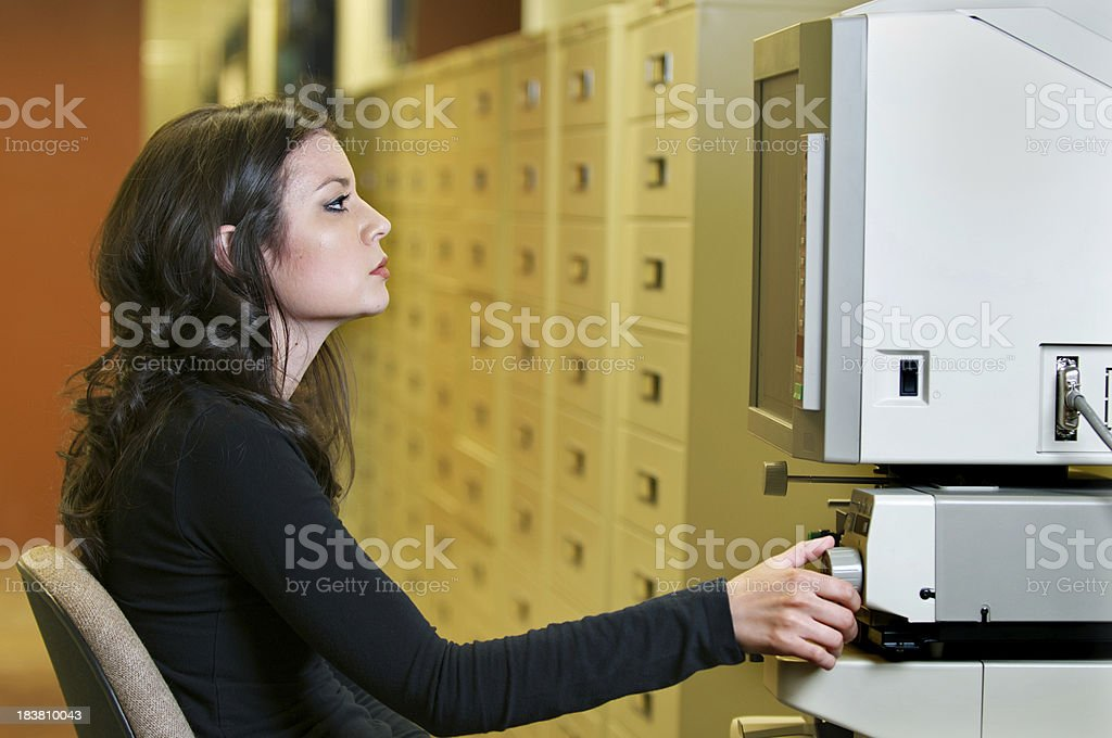 Young Woman Reading Microfilm or Microfiche stock photo