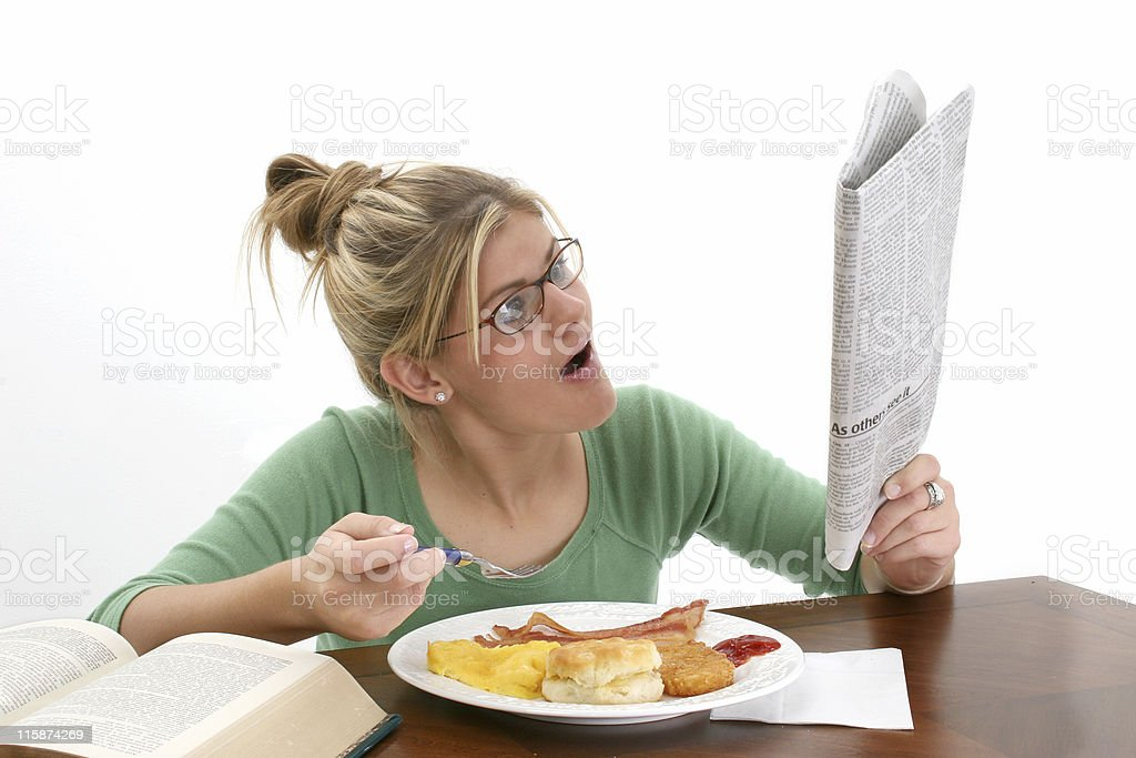 Young woman reading newspaper at breakfast royalty-free stock photo