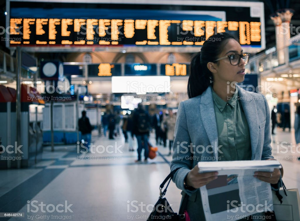 young woman reading newspaper at the station stock photo