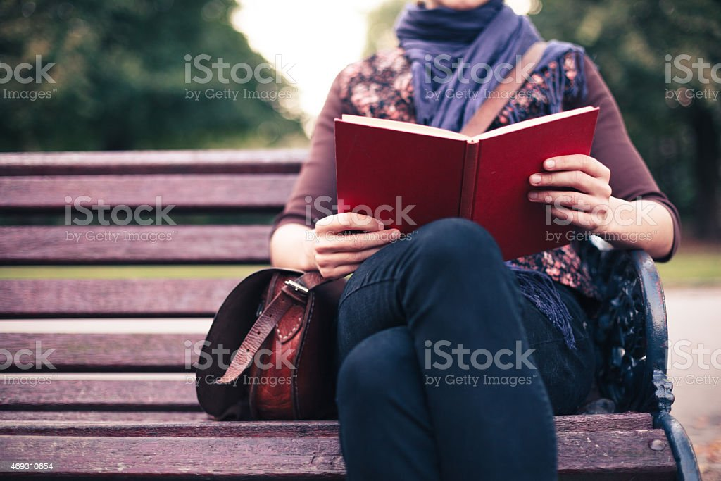 Young woman reading on park bench stock photo