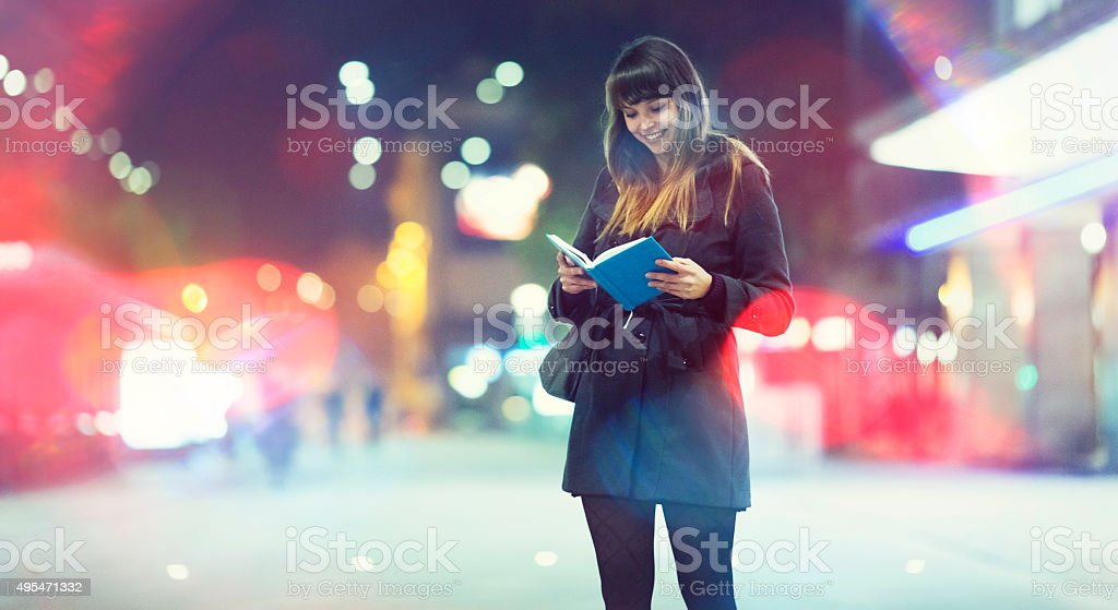 Young woman reading on the street, waiting stock photo