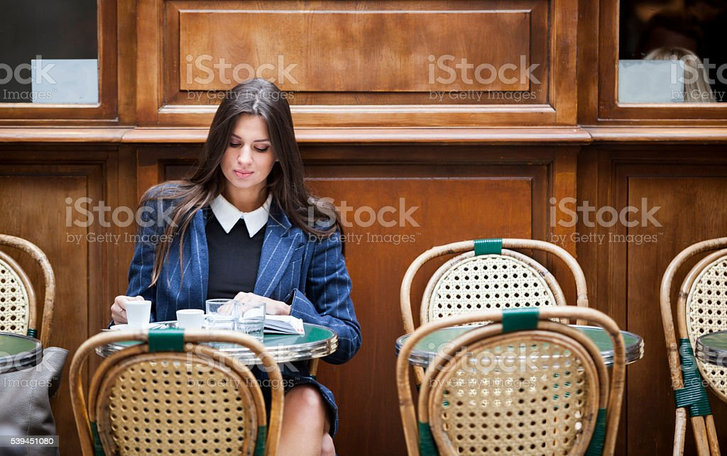 Young Woman Reading While Having Coffee In A Restaurant stock photo