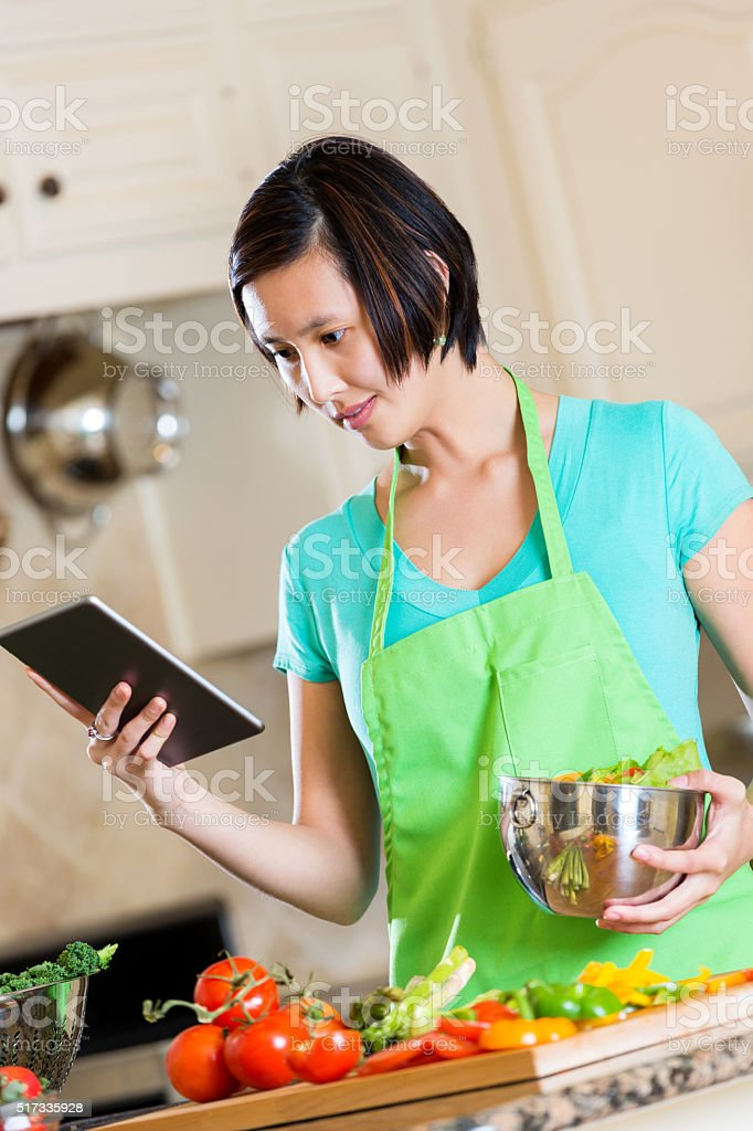 Young woman reads recipe on digital tablet stock photo