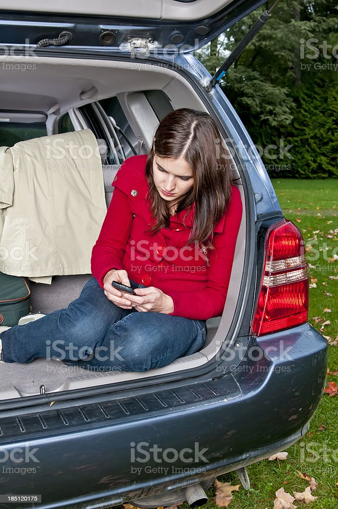 Young woman ready to travel texting on her cell phone stock photo