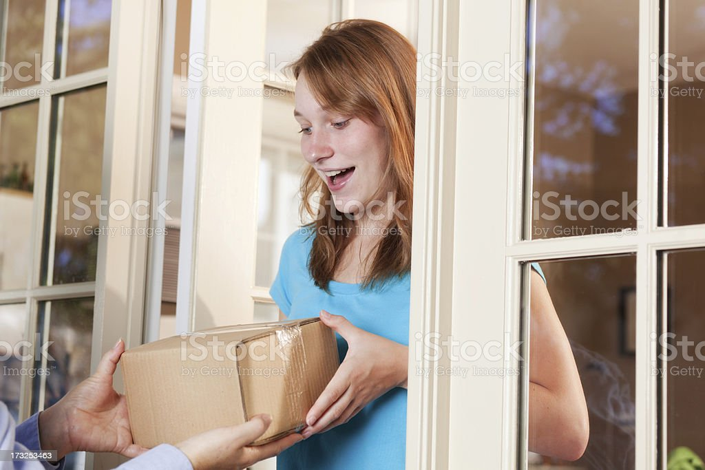 Young Woman Receiving a Package from Delivery Service Hz stock photo