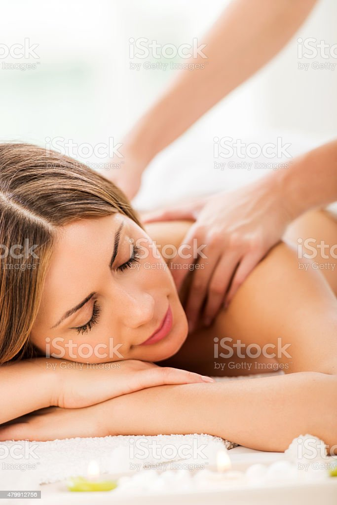 Young woman receiving back massage at spa. stock photo