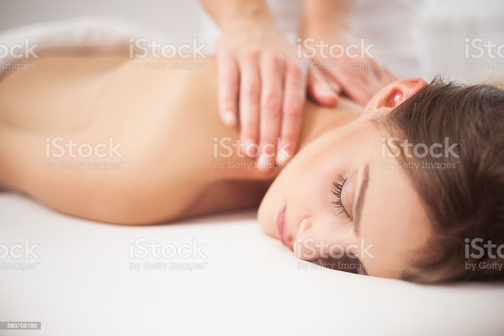 Young woman receiving back massage at spa stock photo