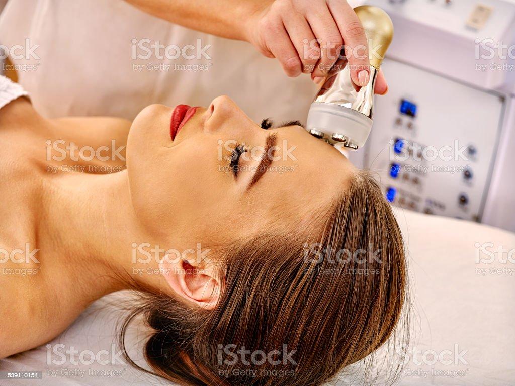 Young woman receiving electric facial massage. stock photo