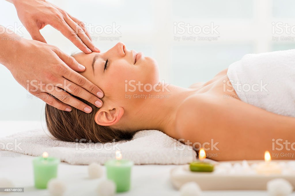Young woman receiving head massage at spa. stock photo