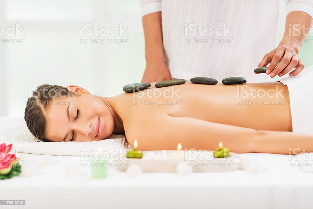 Young woman receiving hot stone therapy treatment. stock photo