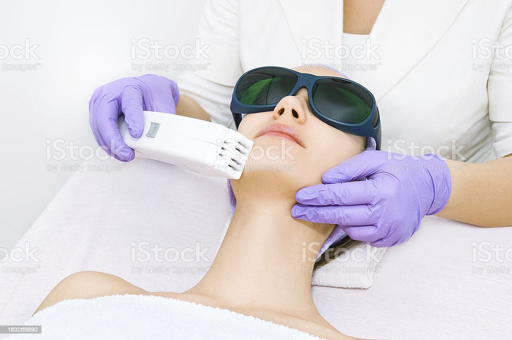 A young woman receiving laser therapy on her face stock photo