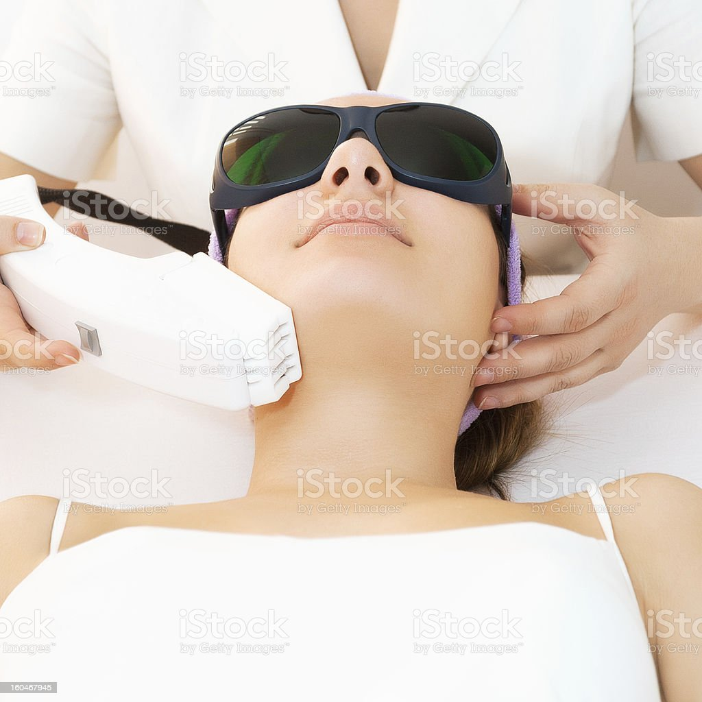 Young woman receiving laser therapy stock photo
