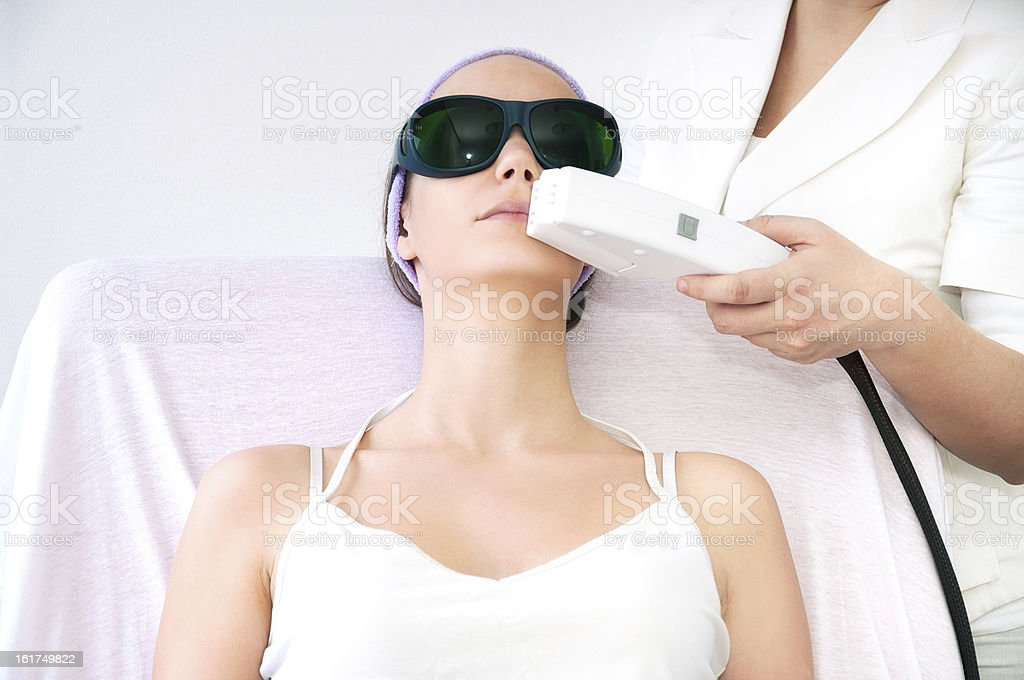 Young woman receiving laser treatment on her face royalty-free stock photo