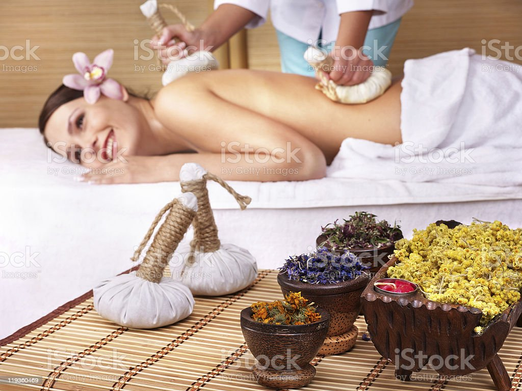 Young woman receiving massage with dried flowers royalty-free stock photo